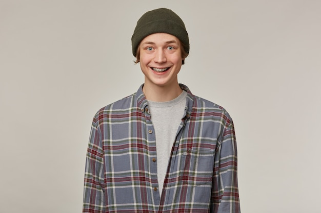 Cheerful guy, happy looking man with blond hair. wearing checkered shirt and beanie. has braces. people and emotion concept. watching positive  isolated over grey wall
