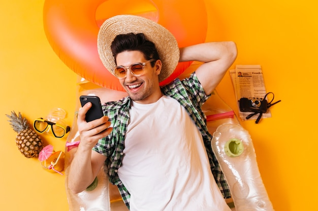Cheerful guy in hat is chatting on phone while lying on inflatable mattress on orange space.