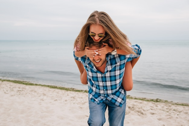 Веселый парень держит свою подругу за спиной, пока она закрывает глаза руками