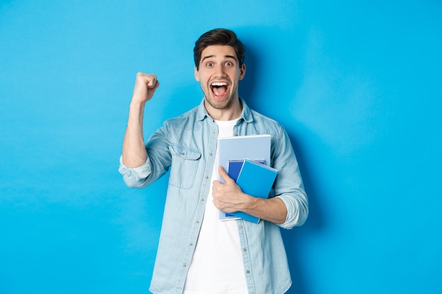Cheerful guy holding notebooks and celebrating, making fist pump and shouting yes with excitement, standing over blue wall