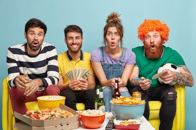 陽気な男はお金の紙幣に束を持ち、サッカーの試合結果に賭け、おいしいピザを食べ、冷たいビールを飲み、ソファで一緒にポーズをとります。スポーツトーナメントを見ながら4人の友人がギャンブル