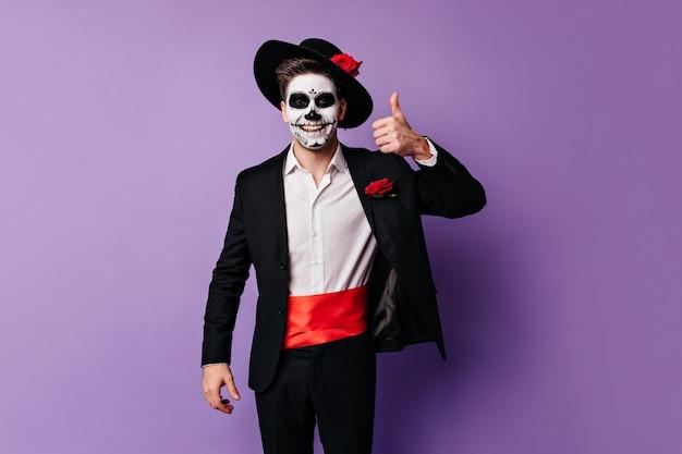 좋은 분위기의 쾌활한 남자는 할로윈 파티 의상을 입고 포즈를 취하는 엄지 손가락을 보여줍니다.