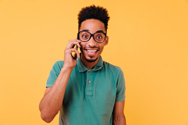電話で話しているトレンディな緑のtシャツの陽気な男。スマートフォンを持って笑顔でのんきな青年。