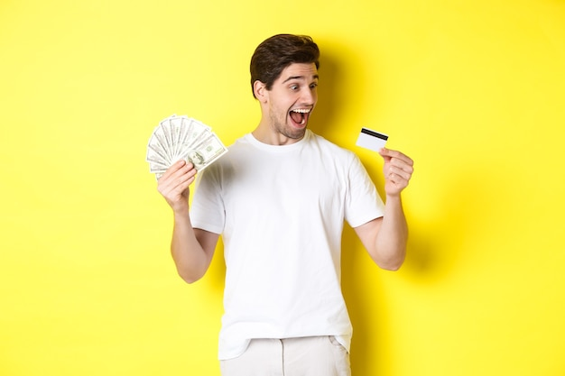 Cheerful guy looking at credit card, holding money, concept of bank credit and loans, standing over yellow background.