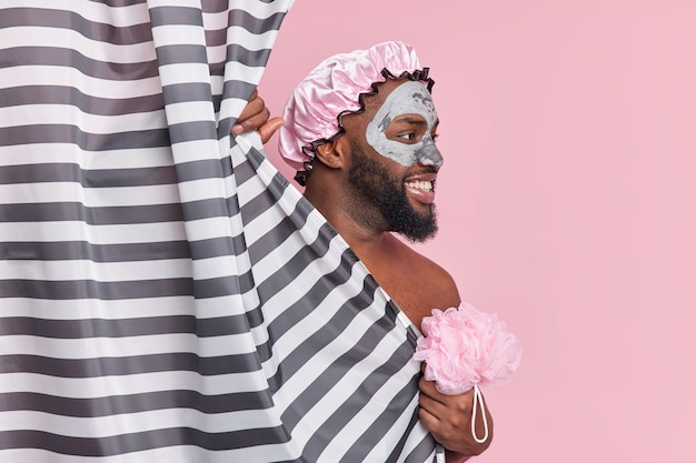 Cheerful guy looks cheerfully aside has thick beard wears bath hat and nourishing beauty mask holds sponge and cleans body hides behind shower curtain isolated over pink wall
