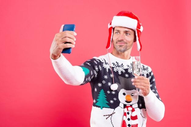 赤い背景のスマートフォンで自分撮りを作る陽気な男。ポジティブな感情を表現します。シャンパンを飲みます。乾杯。メリークリスマス。年末年始を祝います。冬のセーターと赤い帽子の男。