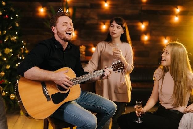Веселый парень в праздничной шляпе играет на гитаре и поет перед друзьями на новогодней вечеринке в красивом доме. рождественская елка с гирляндой и стеной с праздничным освещением в фоновом режиме.