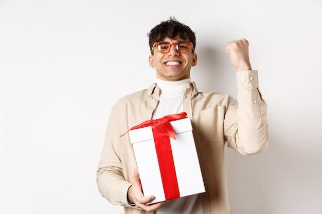 쾌활한 남자는 선물을 받고, 주먹을 펄럭이며 기뻐하며 흰색 배경에 서서 선물을 받았습니다.