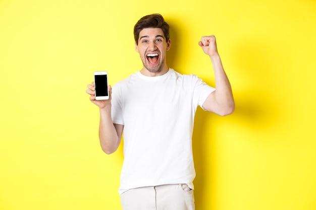 Веселый парень показывает экран смартфона, поднимает руку и празднует, торжествуя над интернетом