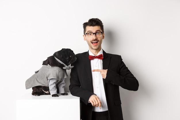 그의 귀여운 퍼그와 함께 서 있는 쾌활한 남자, 흰색 배경 위에 포즈 파티 의상을 입고 개를 가리키는 손가락.