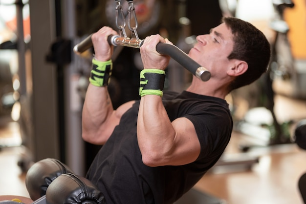 Cheerful guy training dorsal muscles by taking handles and bringing them down.