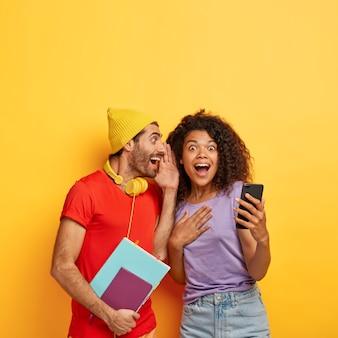 Веселый парень шепчет секрет подруге, делится сплетнями, развлекается после занятий, возбужденная кудрявая женщина держит сотовый телефон, получает интересную информацию от однокурсницы. два студента что-то обсуждают