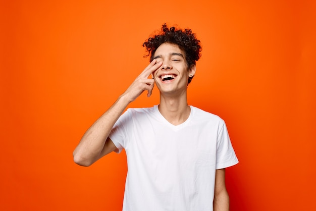 Cheerful guy in white t-shirt hand gesture emotions isolated on orange background