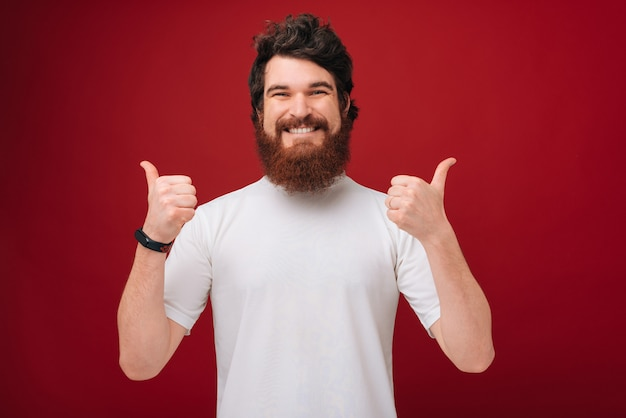 Веселый парень с бородой показывает палец вверх над красной стеной