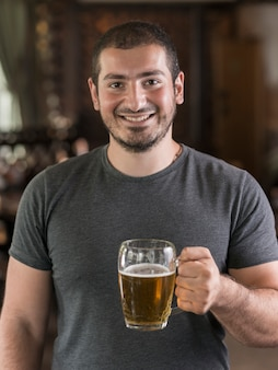 Cheerful guy with beer in bar