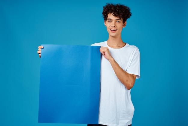 孤立した背景を宣伝する巻き毛の青いモックアップポスターと陽気な男