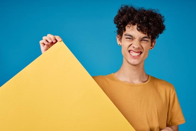 Веселый парень с кудрявыми волосами из желтых астр в голубых руках
