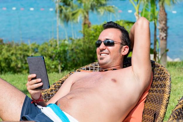 Ragazzo allegro con il suo cellulare a riposo all'aperto