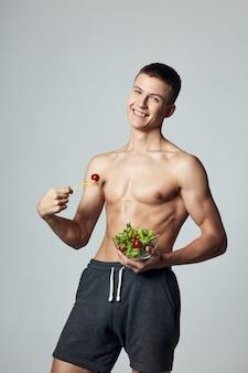 ポンプアップされた筋肉腹筋プレートサラダダイエット食品孤立した背景を持つ陽気な男