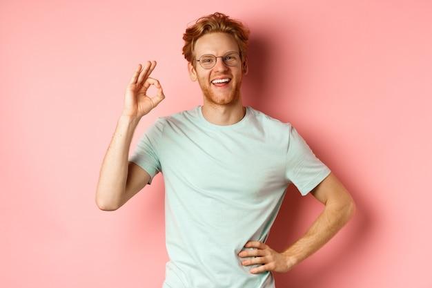 Веселый парень с рыжими волосами и бородой, в очках, показывая ок, подписывается в знак одобрения и говорит «да», удовлетворенно улыбаясь, стоя на розовом фоне.