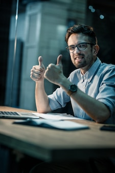 Cheerful guy with thumbs up in office