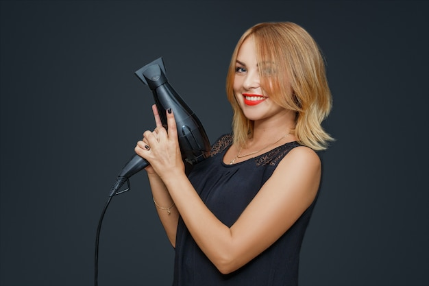 Cheerful hairdresser, woman posing with a hairdryer in her hands