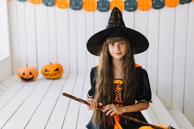 Cheerful halloween witch holding broom