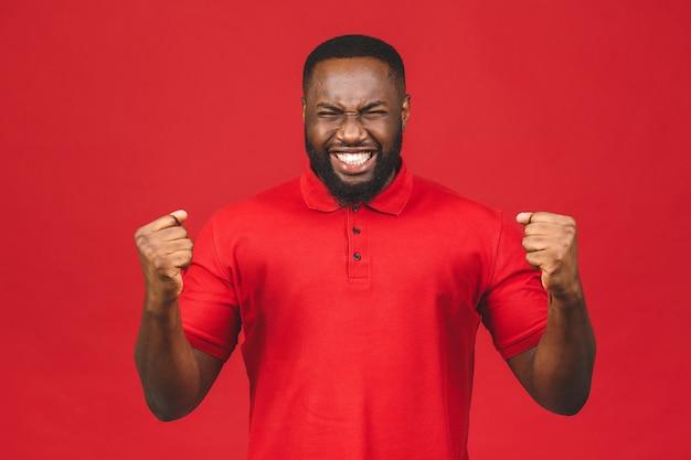 勝利に興奮しながらイエスのジェスチャーをする陽気なハンサムなアフリカ系アメリカ人の男