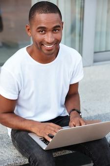 陽気なハンサムなアフリカ系アメリカ人の若い男が座って、屋外でラップトップを使用しています