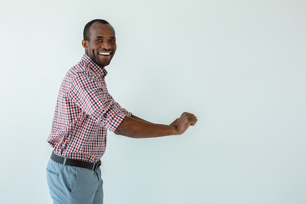 Cheerful handsome afro american man moving the cart against white wall