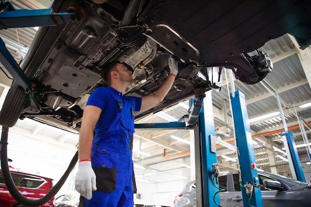 オーバーオールの陽気でハンサムで自信に満ちた車の修理スペシャリストは、サービス中のリフトで車の古い部品を新しい部品に修理して交換します
