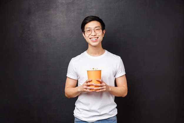 Cheerful handsome asian boyfriend bought popcorn for girlfriend while having date at cinema, smiling watching hilarious comedy, chuckle funny joke, enjoying leisure time on weekends,