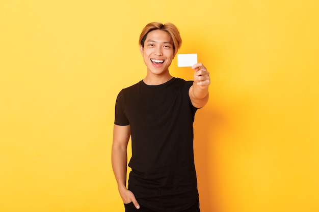 Cheerful handsome asian guy smiling pleased and showing credit card
