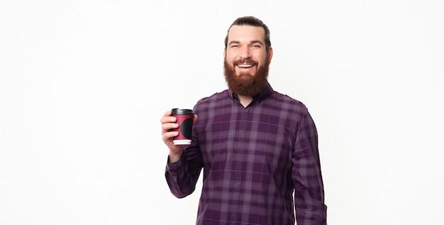 持ち帰るためにコーヒーのカップを保持している陽気なハンサムなひげを生やした男