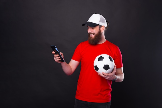 Cheerful handsome bearded man holding soccer ball and tablet over black background