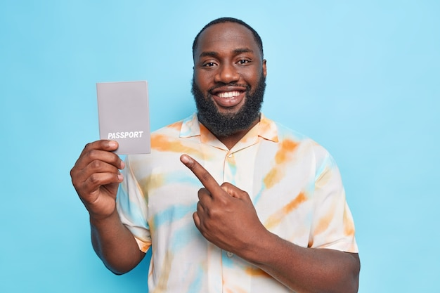 Cheerful handsome bearded man with dark skin points at passport happy about future travel smiles broadly dressed in washed out t shirt isolated over blue wall