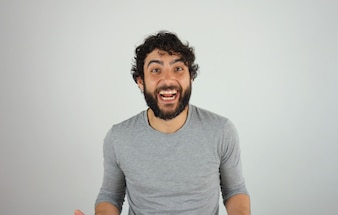 Cheerful handsome brunette man with beard and curly hair studio portrait