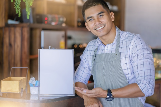 Cheerful handsome business owner standing with invite present menu in front of bar.
