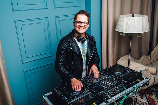 Cheerful handsome dj playing music in vintage interior