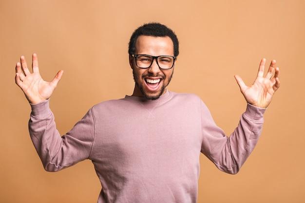 勝つことに興奮しながらイエスのジェスチャーをする陽気なハンサムな男。恍惚とした若いファンの応援とサポートの表現
