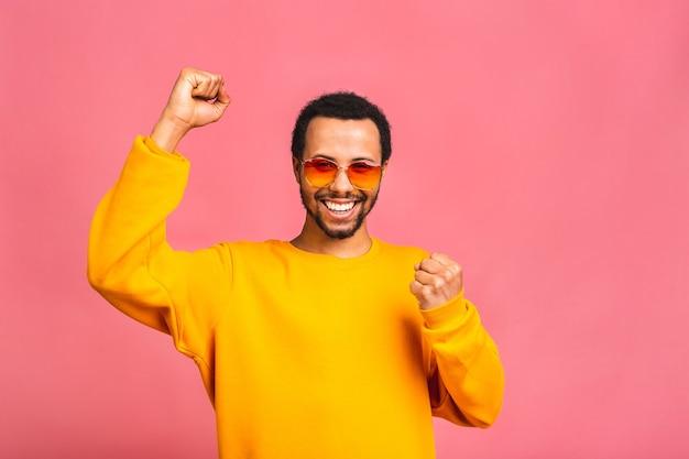 勝つことに興奮しながらイエスのジェスチャーをする陽気なハンサムな男 Premium写真