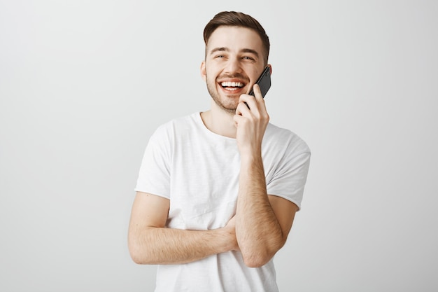 Cheerful handsome guy talking on phone, calling friend