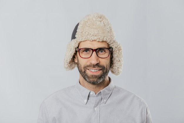 Cheerful handsome guy wears warm winter cap with earflaps, spectacles and white shirt