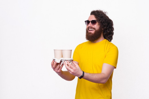 Cheerful handsome hipster man with long hair giving someone two cups of coffee to go