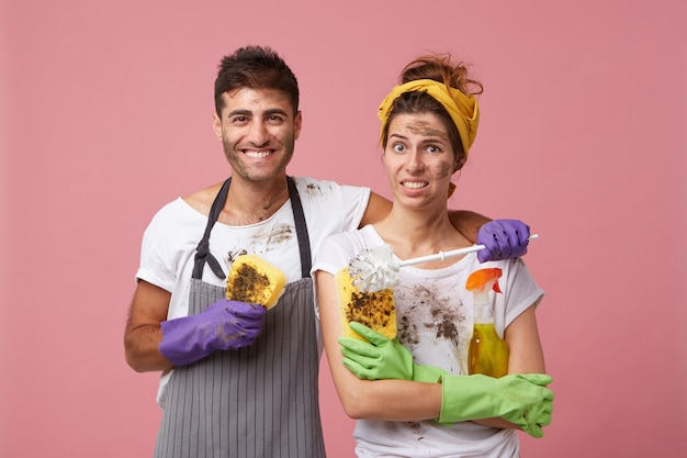 Cheerful handsome male wearing protective gloves and apron holding dirty sponge embracing his wife