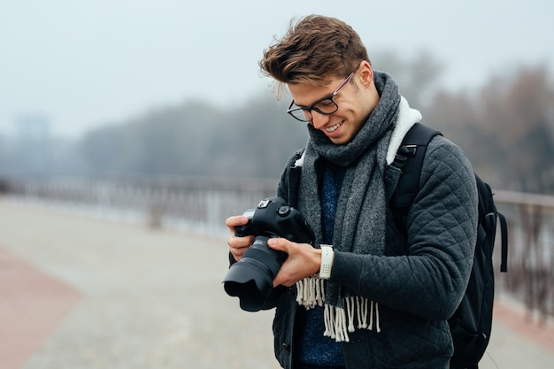 Cheerful handsome man in eyeglasses looks at photos in the camera.