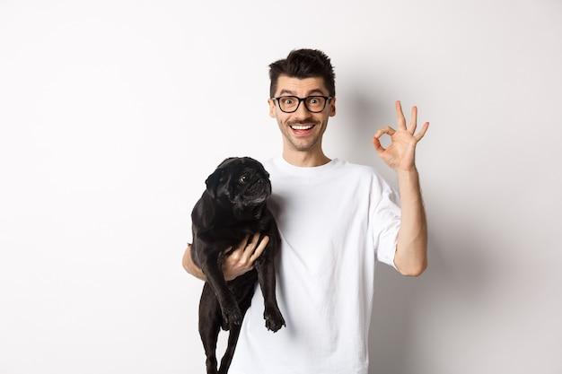 犬を保持し、大丈夫な兆候を示し、白い背景の上に立って、ペット関連製品を承認または推奨する陽気なハンサムな男