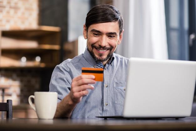Веселый красавец держит свою кредитную карту, используя свой ноутбук