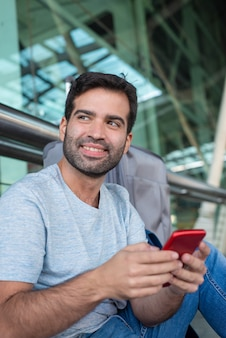 Cheerful handsome man holding smartphone at airport