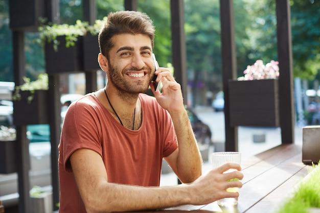 Веселый красавец смеется и улыбается во время разговора по мобильному телефону из летнего кафе